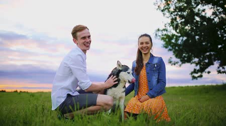 fancier : family, pet, animal and people concept - happy couple with labrador retriever dog walking in city park