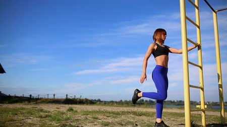 quads : The girl in the blue leggings kneads feet on a vertical ladder. Stretches the muscles and preparing for training outdoors on blue sky background.