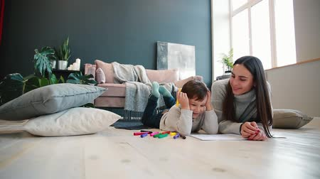 etnisite : Beautiful young mother in a warm sweater lying on the floor with my son drawing with markers on paper portraying his family. The child learns to draw. Stok Video