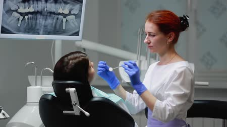 farag : The dentist completes his work with a patient. Removes Bor machine and gives a girl a mirror to assess the work. The girl looks at your teeth and thanked the dentist. Stock mozgókép