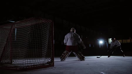jogador : Professional hockey players play the shootout. The player who takes the penalty a hockey goalkeeper. Steadicam.