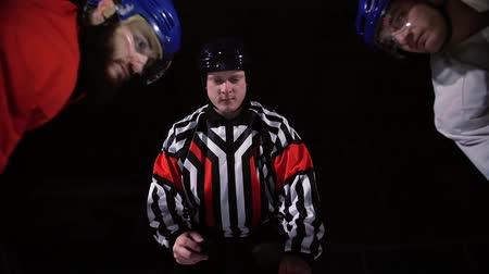 faceoff : hockey referee produces a faceoff and the two players begin to fight for the puck. slow motion