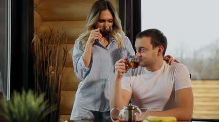 любовь : Beautiful woman in pajamas pours her husband tea, hugging him in the kitchen and drink tea. Lovers.