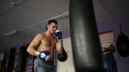 sağlam : Muscular male professional boxer trains by punching bag at the gym in Boxing gloves bare-chested.