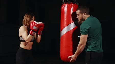 bokszoló : Young beautiful brunette woman in sportswear is training with his Boxing coach. Holds punches with Boxing gloves in pouch on black background. Stock mozgókép