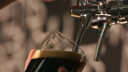 bira fabrikası : The bartender pours a dark beer in glass close-up.