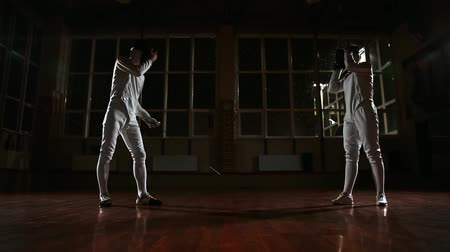 фехтование : Young man and woman dressed in costumes for fencing lessons in the gym. Wear a suit and begin the battle. In the background it is snowing.
