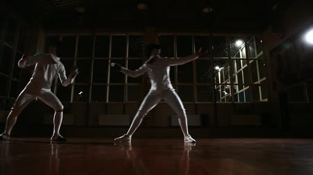 фехтование : Young man and woman dressed in costumes for fencing practice in the sports hall. Back on the background it is snowing. Dynamic horizontal movement of the camera right and left