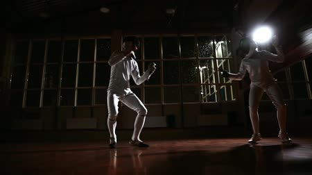 kılıç : Young man and woman dressed in costumes for fencing practice in the sports hall. Back on the background it is snowing. Dynamic horizontal movement of the camera right and left