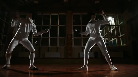 фехтование : Young man and woman dressed in costumes for fencing practice in the sports hall. Back on the background it is snowing. Hitting the slider. zoom