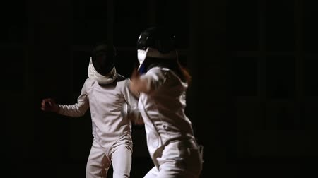 cripple : Young women and men in hats and suits for fencing, fighting with swords. Dark background. Stock Footage