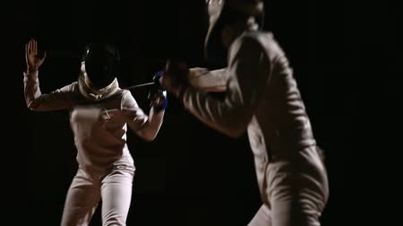 kılıç : Young women and men in hats and suits for fencing, fighting with swords. Dark background. The camera movement around the unit