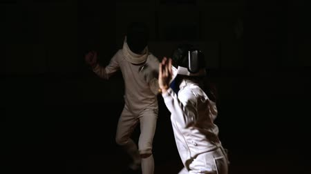 competitivo : Young women and men in hats and suits for fencing, fighting with swords. Dark background. The view from behind the head