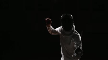 фехтование : A man dressed for fencing and mask hand adjusts his rapier. Focus on the sword.