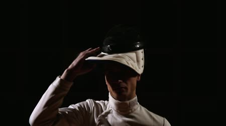 фехтование : the camera moves upwards showing the costume of the swordsman who wears a helmet and prepares for battle Стоковые видеозаписи