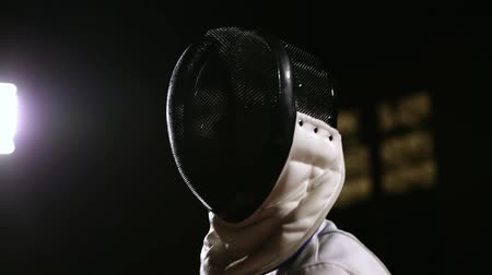 grapple : Closeup of a man in helmet for fencing grapple with an opponent on a dark background. Stock Footage