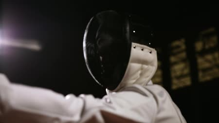 cripple : Closeup of a man wears a helmet for fencing grapple with an opponent on a dark background with a rapier. The camera moves from the bottom up.