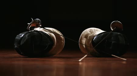 фехтование : Closeup on the floor on the mask and rapier for fencing. A man and a woman come and pick them up.