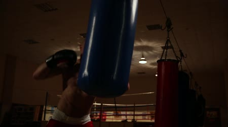 muscular build : A professional boxer conducts training on a boxer pear for working off punches.