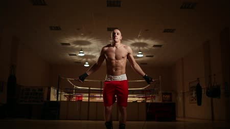 груша : A pumped-up man in boxing shoes and shorts in the gym against the backdrop of a boxing ring. The camera moves on a Steadicam