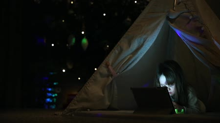 nativo : Sitting at home in a tent against the background of a Christmas tree, a little girl lying on the floor talking on video communication, learns to use a tablet computer. Close-up