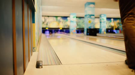 tópicos : In the game club for bowling, the player throws a bowling ball that knocks down skittles. The player knocks out the strike and is happy with the victory.
