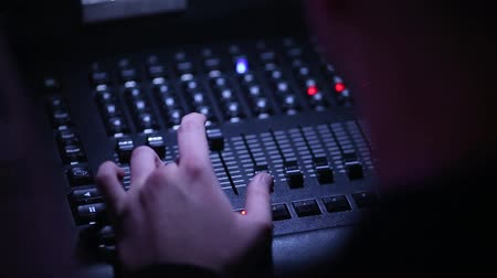atitude : A close-up of a mans hand controls the sound equipment at a concert of a famous band. The sound panel. Stock Footage