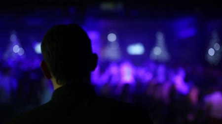 concert hall : Close-up of a DJ head view from behind, and on a blurry background bokeh dancing judi at a party