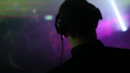 concert hall : Back view. The back and headphones of the DJ in the foreground, the dancing people are blurred. Stock Footage