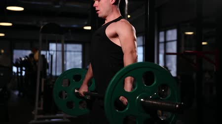 lift ups : A sports athlete in the gym raises the bar with a weight above his head from the sitting position. close-up camera moves from bottom to top. Stock Footage