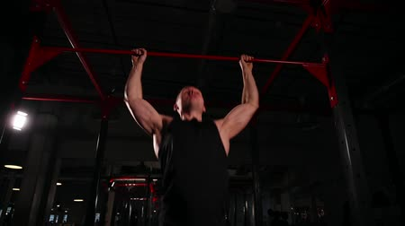 lift ups : dynamic movement of the camera, a man in black sportswear is pulling on the bar, then goes to the exercise with the bar.