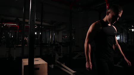 lift ups : A circular cardio training designed for a set of exercises, a man in a black T-shirt and black pants, harnesses a cube and after this performs a bicep exercise with a barbell. Stock Footage