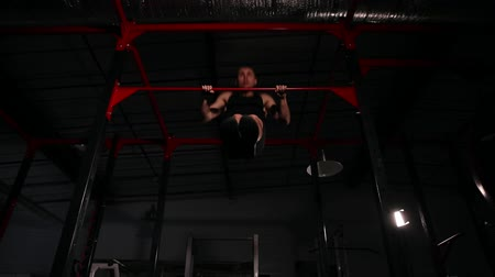 lift ups : The athlete in black clothes in the gym performs a power outlet on the horizontal bar. A wide angle view from below.