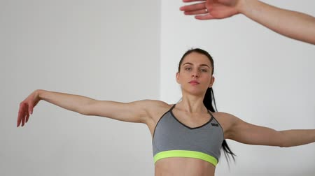 ativo : Beautiful girls perform slopes in the side on their knees, exercises for Pilates. Smooth movements of hands while practicing yoga. Close-up camera moves from one girl to another