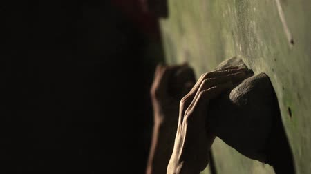 ügyesség : Close-up of a climbing wall, hand grasping a stone. Slow motion