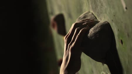 bouldering : Close-up of a climber climbs on a stone wall indoors. The Sculpture. The hand is fixed at the finish. The exercise is completed.