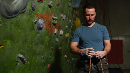 ügyesség : A climber man prepares the equipment against the backdrop of a climbing wall. Knit knot for climbing a mountain.