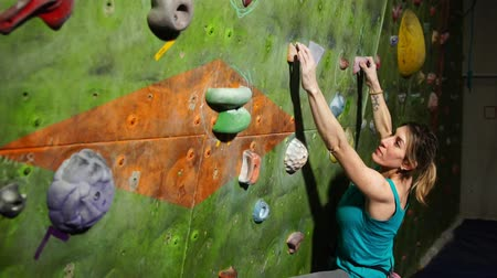skalní útes : A female boulder trains to overcome obstacles on the wall for climbers. Professional rescuer. Climbing Wall