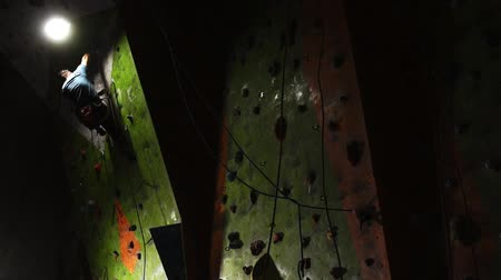 bouldering : A man on a safety rope climbs the rock up. Slow motion Stock Footage