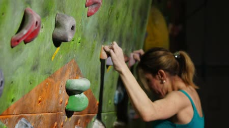bouldering : A female boulder trains to overcome obstacles on the wall for climbers. Professional rescuer. Climbing Wall. competitions without insurance. Stock Footage