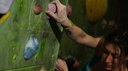 ügyesség : A female boulder trains to overcome obstacles on the wall for climbers. Professional rescuer. Climbing Wall.