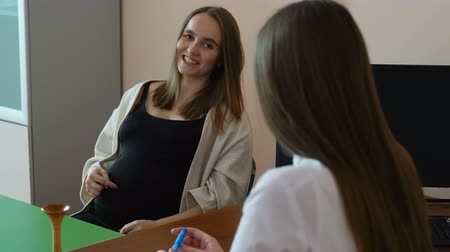 gynaecologist : A young obstetrician woman gynecologist takes a pregnant patient in her office in the hospital. A pregnant woman asks questions and keeps her hands on her stomach. Young women