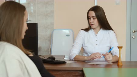 gynaecologist : The pregnant patient will learn the results of the tests from her doctor. woman doctor gives recommendations for caring for a child Stock Footage