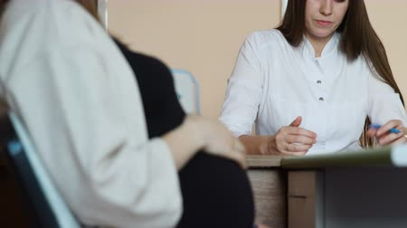 gynaecologist : A young beautiful pregnant woman in a black T-shirt is talking to a young female doctor in a white coat in her office in the hospital. Consultation of doctor and patient. The doctor prescribes manual for treatment