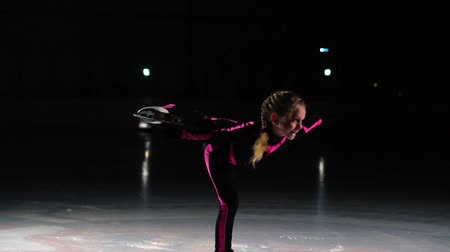 konkurenční : Little girl skater performs a spinning standing in the arena of the ice stadium. Holds a skate with one hand