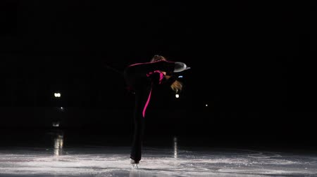 medalha : A little girl skater in a black sports suit and white skates performs a spinning stand in the arena of the ice stadium. Standing on one leg to hold the blade with your hand. Professional figure skater.