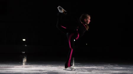 medal : A little girl skater in a black sports suit and white skates performs a spinning stand in the arena of the ice stadium. Standing on one leg to hold the blade with your hand. Professional figure skater. Raise your leg above the head in competitions