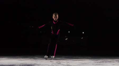 medalha : the girl skater rides into the frame on skates and looks directly into the camera. The camera on the stylus moves along with it in the course of travel. Backlight on the ice arena.