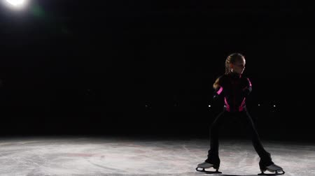 medal : A professional girl skater moves in a circle on ice on skates in position when the feet are deployed to the sides, and the camera moves along with it. Delayed shooting professional skating. Backlight. Dark background.