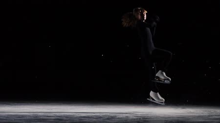 medal : A professional woman, figure skater to a black suit at the competitions in figure skating, performs a triple revolution around her axis in the jump. And ends the program with a bow. Stock Footage